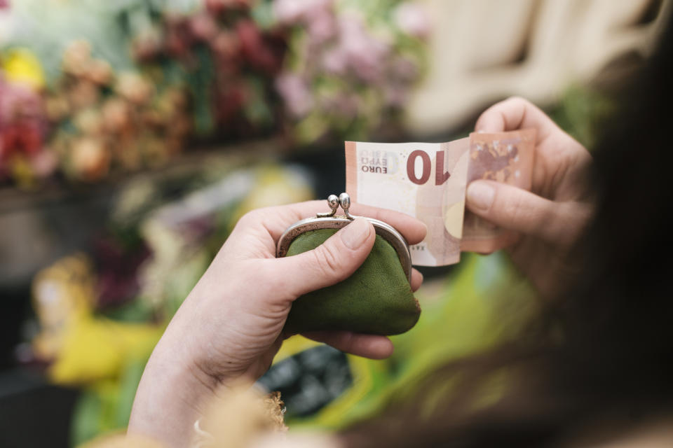 Close-up of woman paying for Flowers with a 10 Euro Bill at an outdoor Market.