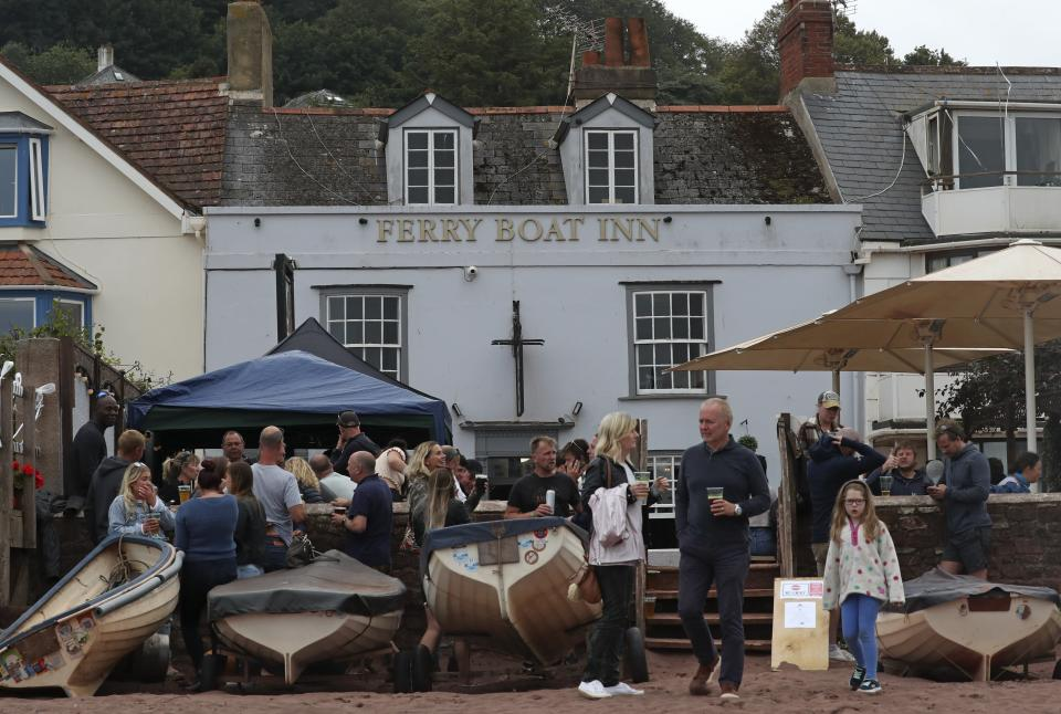 People enjoy a drink outside the Ferry Boat Inn in Shaldon, England, Saturday, July 4, 2020. England embarked on perhaps its biggest lockdown easing yet as pubs and restaurants have the right to reopen for the first time in more than three months. (AP Photo/Tony Hicks)