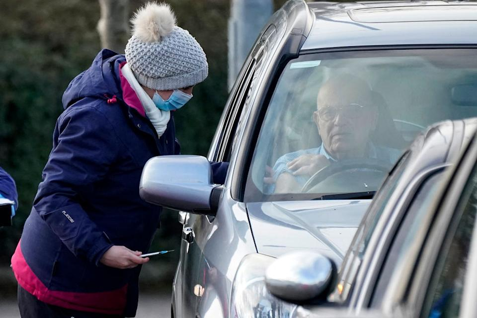 A man sits in his car as he is administered the Pfizer/BioNTech coronavirus vaccine at a drive-thru COVID-19 vaccination centre at Hyde Leisure Centre in Hyde, England.