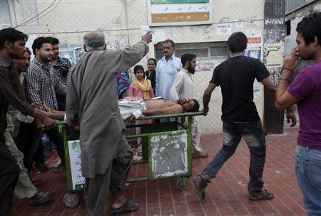 Rescue workers and relatives wheel an injured man on a stretcher, who was attacked by unknown gunmen, at Civil Hospital in Karachi March 12, 2014. REUTERS/Athar Hussain