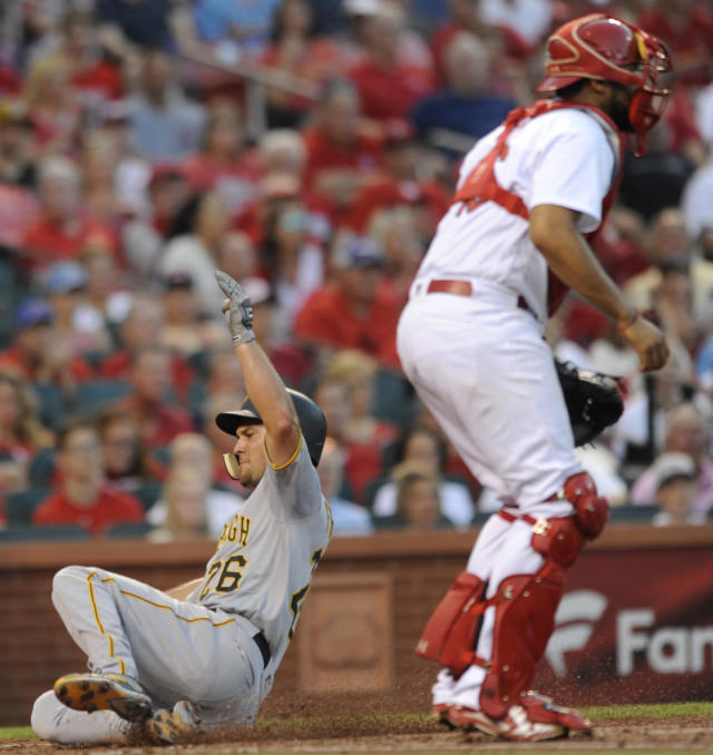 Pittsburgh Pirates' Adam Frazier (26) scores on a sacrifice fly by teammate Josh Bell as St. Louis Cardinals' Francisco Pena waits for the ball during the third inning of a baseball game Friday, June 1, 2018, at Busch Stadium in St. Louis. (AP Photo/Bill Boyce)