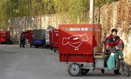 Chen Honglei, a 26-year-old courier of Jingdong, also known as JD.com, prepares his electric tricycle before leaving the company's Haidian district delivery station in Beijing, in this November 20, 2013 file photo. REUTERS/Paul Carsten/Files