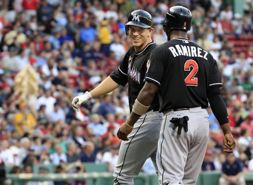 Miami Marlins' Logan Morrison, left, turns to smile at Hanley Ramirez (2) as they walk back to the dugout after Morrison's two-run homer against the Boston Red Sox in the first inning of an interleague baseball game at Fenway Park in Boston on Tuesday, June 19, 2012. (AP Photo/Elise Amendola)