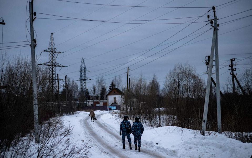 Officers of the Russian Federal Penitentiary Service walk near the gate of penal colony No. 2 - DIMITAR DILKOFF/AFP