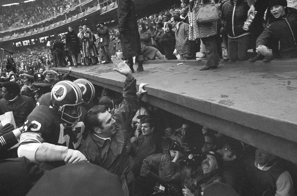 "FILE- In this Dec. 24, 1972, file photo, Washington Redskins coach George Allen waves to fans at Robert F. Kennedy Stadium in Washington as he leaves the field following the team's 16-3 win over the Green Bay Packesr in an NFL playoff game. At left is linebacker Harold McLinton. Washingtons NFL team will get rid of the name ""Redskins"" on Monday, July 13, according to multiple reports. Its unclear when a new name will be revealed for one of the leagues oldest franchises. The team launched a ""thorough review"" of the name July 3.(AP Photo, File)"