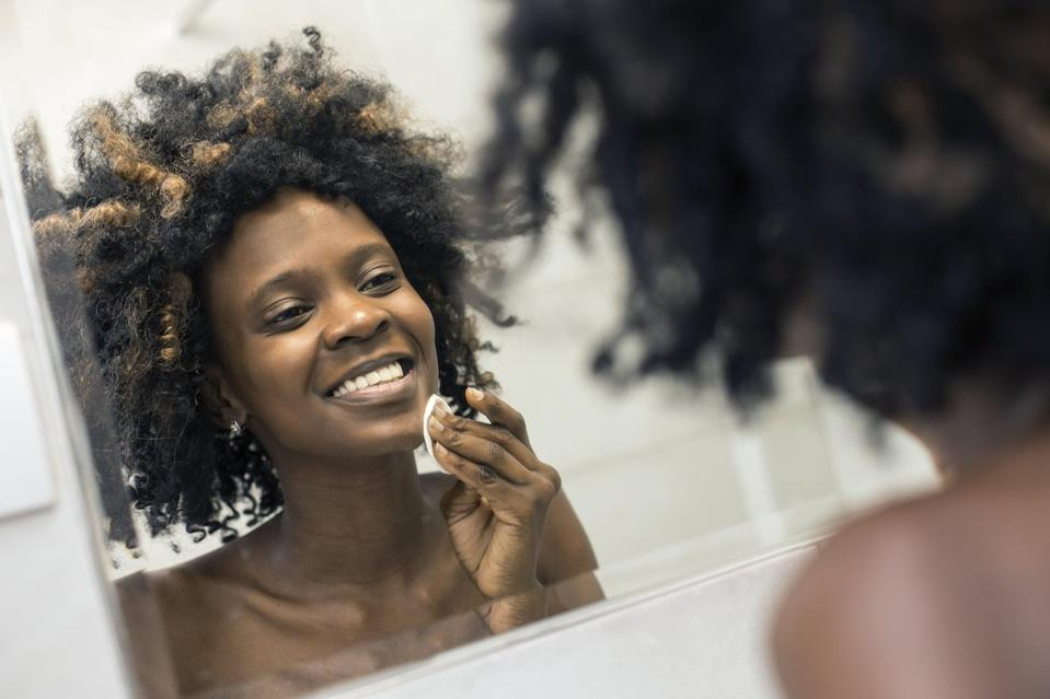 Young woman cleaning her skin in bathroom mirror with a cotton pad. About 25 years old, African female with curly hair.
