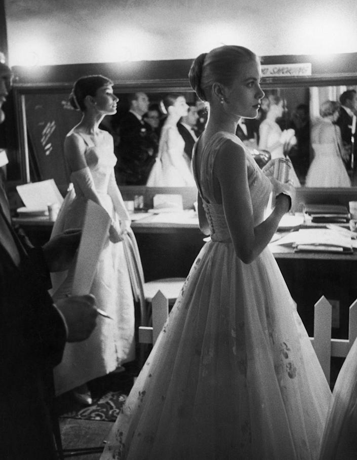 <p>Kelly and Audrey Hepburn wait in the wings of the 1956 Academy Awards as they prepare to present on stage. Kelly presented the Oscar for Best Actor to Ernest Borgnine. </p>