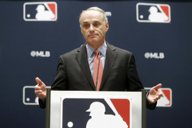 FILE - In this Nov. 21, 2019, file photo, baseball commissioner Rob Manfred speaks to the media at the owners meeting in Arlington, Texas. Major League Baseball is cutting the salary of senior staff by an average of 35% for this year and is guaranteeing paychecks to its full-time employees of its central office through May. Baseball Commissioner Rob Manfred made the announcement Tuesday, April 14, 2020. (AP Photo/LM Otero, File)