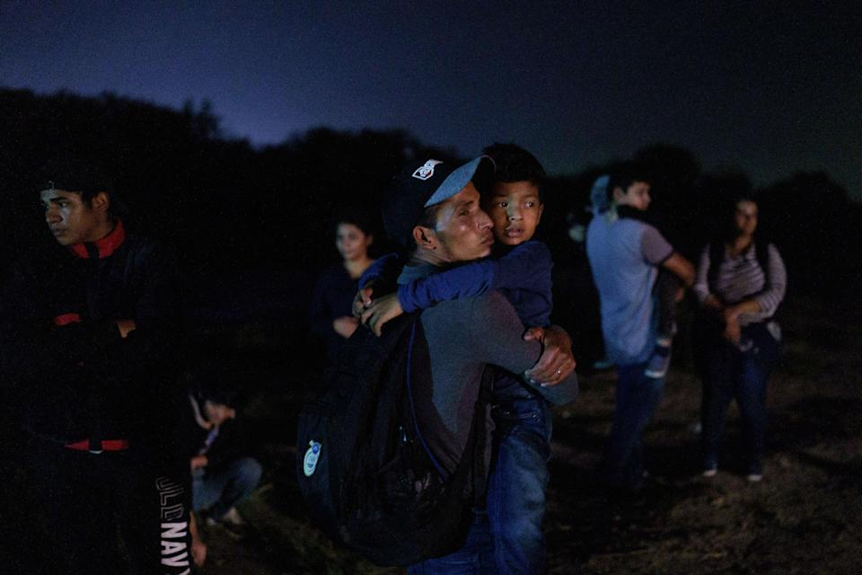 Honduran Eric Villanueva, 31, holds his son Eric, 7, while waiting to be led to a United States Border Patrol processing area after crossing the US-Mexico border on a raft into the United States in Roma, Texas late on July 9, 2021. / Credit: PAUL RATJE/AFP via Getty Images
