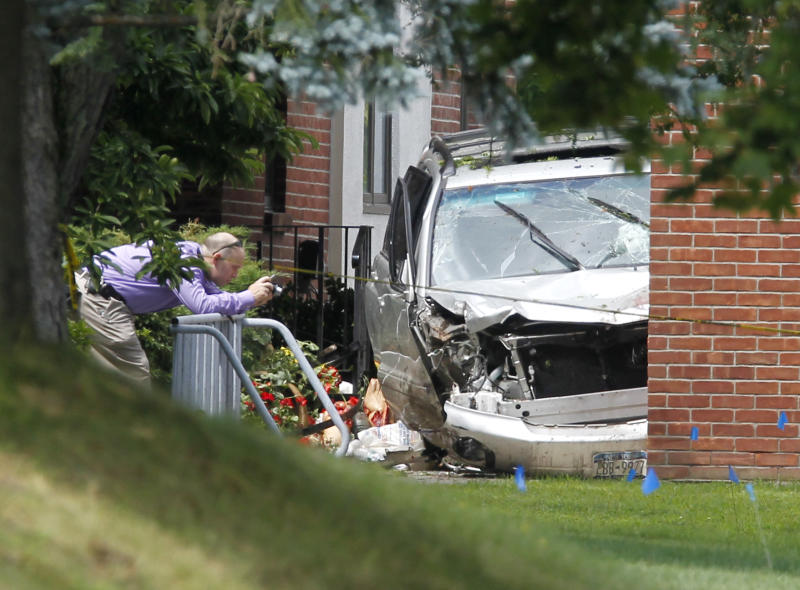 A law enforcement official photographs a vehicle in front of St. Matthews Roman Catholic Church in Voorheesville, N.Y., where three pedestrians were killed, on Wednesday, Aug. 10, 2011. Acting Albany County Sheriff Craig Apple said a 57-year-old woman was driving the van when it accelerated off the road and hit the group at about 8:30 a.m. outside St. Matthew's Roman Catholic Church in Voorheesville, an Albany suburb. He said the driver's foot or a flip-flop she was wearing apparently interfered with the van's gas pedal.  The driver was being treated at Albany Medical Center for injuries that weren't life-threatening. (AP Photo/Mike Groll)