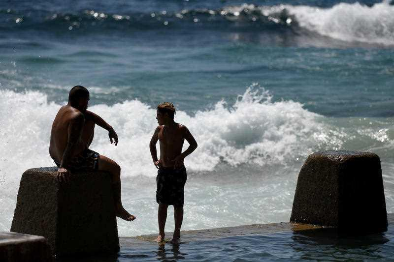 Beachgoers are seen at Ross Jones Rockpool in Coogee during hot weather in Sydney.