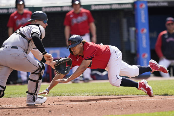 Cleveland Indians' Josh Naylor, right, slides safely into home plate as Chicago White Sox catcher Zack Collins waits for the ball in the fourth inning of the first baseball game of a doubleheader, Monday, May 31, 2021, in Cleveland. (AP Photo/Tony Dejak)
