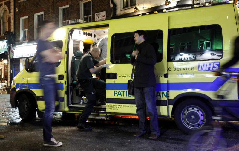 """A man is taken into the ambulance, known as a """"booze bus,"""" dedicated to keeping drunk people out of trouble on the streets, and out of hospital emergency rooms in the Soho area of central London area of Soho late Friday, April, 21, 2012. Binge drinking has reached crisis levels in Britain, health experts say, costing the cash-strapped National Health Service 2.7 billion pounds (US$4.4 billion) a year, including the cost of hospital admissions related to booze-fueled violence and longer-term health problems. Unlike all other major health threats, liver disease is on the rise in Britain, increasing by 25 percent in the last decade and causing a record level of deaths, according to recent government figures. (AP Photo/Alastair Grant)"""