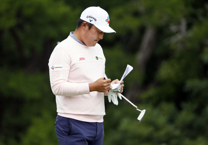 K.H. Lee, of South Korea, looks over his yardage book on the ninth green during the second round of the AT&T Byron Nelson golf tournament in McKinney, Texas, Friday, May 14, 2021. (AP Photo/Ray Carlin)
