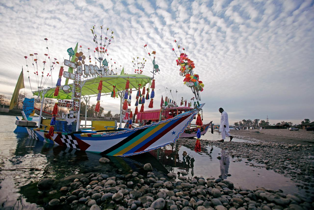 A man walks past decorated water taxi at the bank of the River Kabul at Charsadda, on the outskirts of Peshawar, Pakistan February 25, 2018. REUTERS/ Fayaz  Aziz