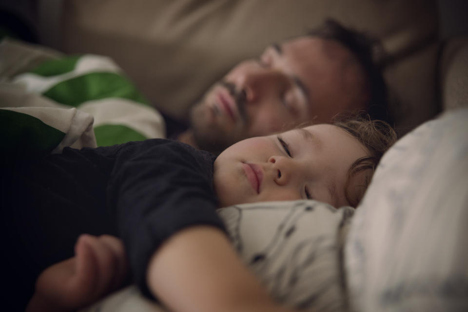 Close up of toddler and dad taking a nap on the sofa