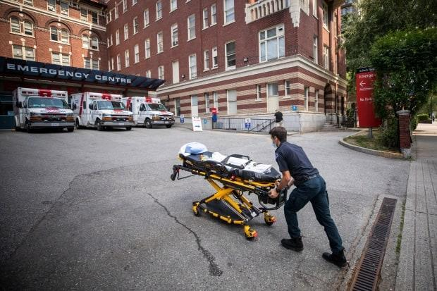 A paramedic outside St. Paul's Hospital in Vancouver on June 30. According to B.C.'s chief coroner, 570 of the 815 sudden deaths recorded over June's week-long heat wave — 70 per cent — have now been deemed 'heat related.' (Ben Nelms/CBC - image credit)