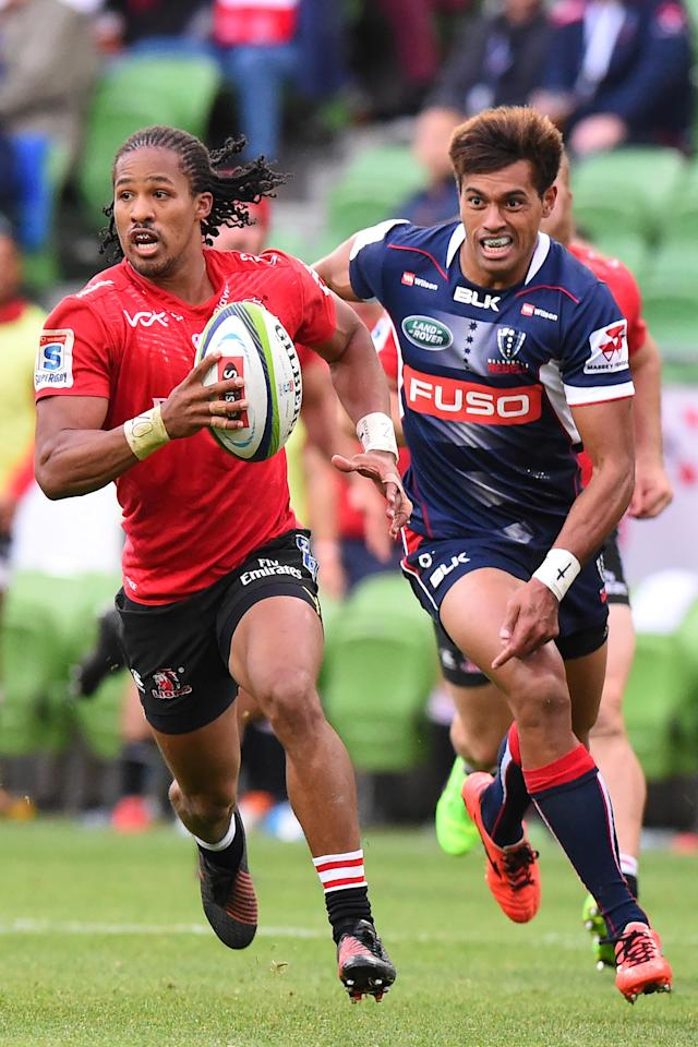 Lions' Sylvian Mahuza (L) runs from Rebels' Ben Volavola during the Super Rugby match between the Melbourne Rebels and Golden Lions at AAMI Park in Melbourne on May 6, 2017. (AFP Photo/Mal Fairclough)