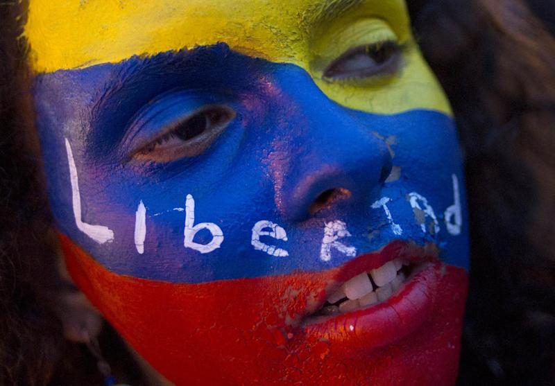 """An anti-government protester with her face painted in the colors of Venezuela's flag with the Spanish word """"Freedom"""" marches in Caracas, Venezuela, Wednesday, April 16, 2014. The opposition wants President Nicolas Maduro's government to free jailed opponents and create an independent truth commission to determine responsibility for deaths tied to protests that have rocked the nation since February. (AP Photo/Ramon Espinosa)"""
