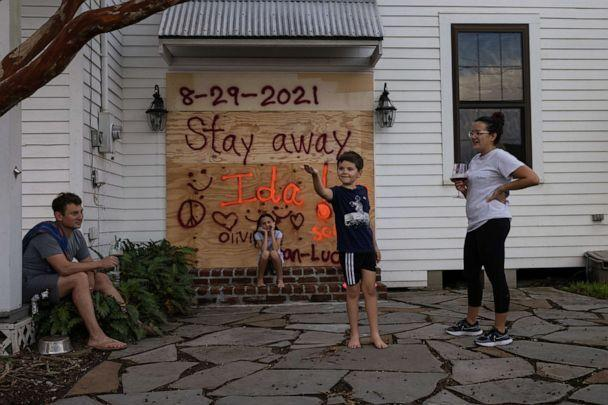 PHOTO: Jean-Luc Bourg, 8, catches a spider in front of his sister Olivia, 10, as his parents Jean Paul and Christina enjoy a glass of wine after boarding up their property in preparation for Hurricane Ida in Morgan City, La., Aug. 28, 2021. (Adrees Latif/Reuters)