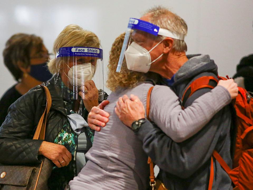 Travelers wearing protective face masks and face shields to prevent the spread of the coronavirus disease (COVID-19) hug at the airport in Denver, Colorado, U.S., November 24, 2020.
