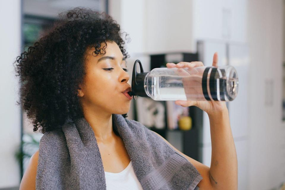 woman drinking water from water bottle while working out