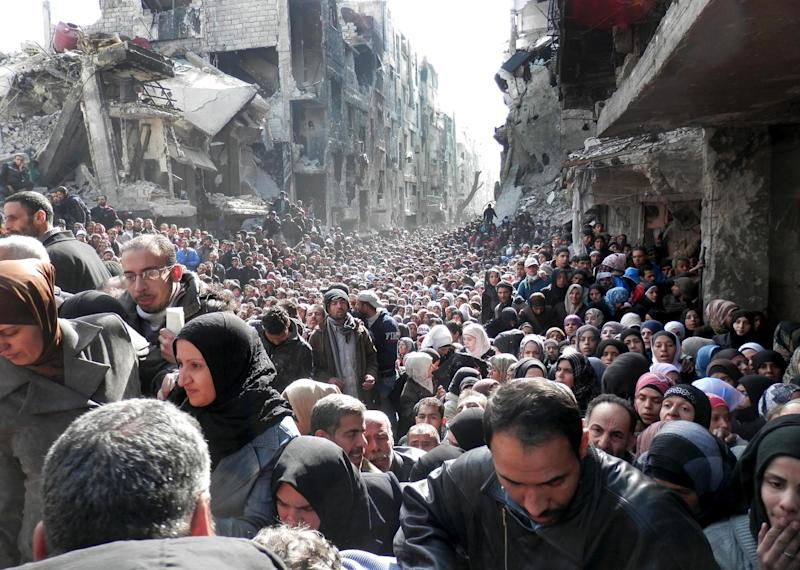 "FILE -- In this Jan. 31, 2014, file photo, released by the United Nations Relief and Works Agency for Palestine Refugees in the Near East (UNRWA), shows residents of the besieged Palestinian camp of Yarmouk, queuing to receive food supplies, in Damascus, Syria. In one besieged neighborhood after another, weary rebels have turned over their weapons to the Syrian government in exchange for an easing of suffocating blockades that have prevented food, medicine and other staples from reaching civilians trapped inside. The government touts the truces as part of its program of ""national reconciliation"" to end Syria's crisis, which has killed more than 140,000 people since March 2011. (AP Photo/UNRWA, File)"