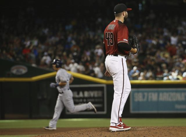 Arizona Diamondbacks starting pitcher Alex Young (49) pauses on the mound after giving up a grand slam to Milwaukee Brewers' Tyler Saladino, left, during the fourth inning of a baseball game Sunday, July 21, 2019, in Phoenix. (AP Photo/Ross D. Franklin)