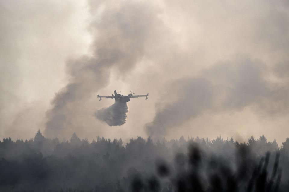 A firefighting plane battles against the fires in the area of Varibobi in Acharnes, north of Athens (Anadolu/Getty)