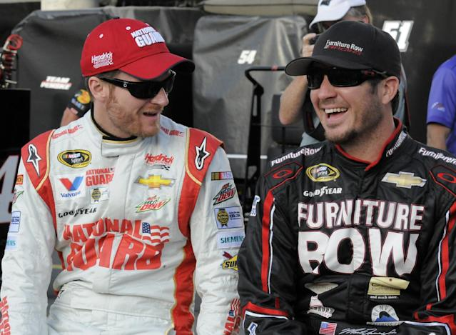 Dale Earnhardt Jr, left, talks with Martin Truex Jr, before qualifying for Sunday's NASCAR Sprint Cup series auto race at Charlotte Motor Speedway in Concord, N.C., Thursday, May 22, 2014. (AP Photo/Mike McCarn)