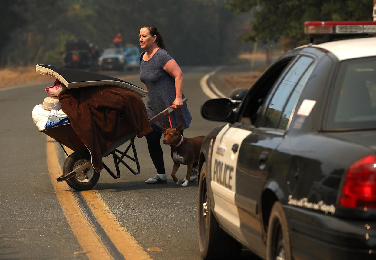 A resident pushes personal belongings in a wheelbarrow as she evacuates ahead of the River fire.