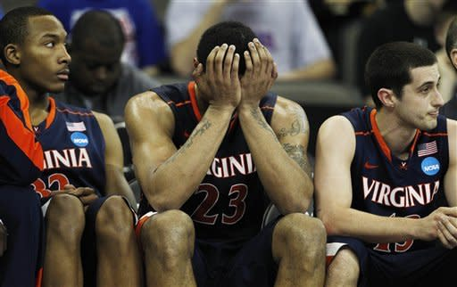 Virginia forward Mike Scott (23) holds his head while on the bench with teammates Darion Atkins (32) and Sammy Zeglinski (13) during the second half of an NCAA college basketball tournament game against Florida at CenturyLink Center in Omaha, Neb., Friday, March 16, 2012. Florida defeated Virginia 71-45. (AP Photo/Orlin Wagner)