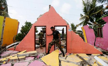 A member of the military inspects a damaged house for victims during a rescue mission after a garabage dump collapsed and buried dozens of houses in Colombo, Sri Lanka April 15, 2017. REUTERS/Dinuka Liyanawatte