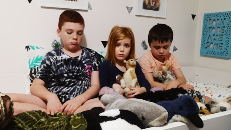 Jack, (11) Heidi, (4) and Sammy (7) sit on a bed in a row. They all look sad.