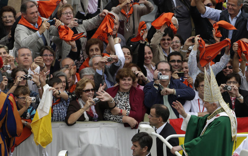 """Pope Benedict XVI, standing on a car at right, waves to faithful as he is leaves after celebrating a mass for the opening of the synod of bishops in St. Peter's Square, at the Vatican, Sunday, Oct. 7 , 2012. Pope Benedict XVI has also named two new """"doctors"""" of the church, conferring the Catholic Church's highest honor on a 16th-century Spanish preacher St. John of Avila, and to St. Hildegard of Bingen, and a 12th— century German mystic who wasn't even officially recognized as a saint until earlier this year. (AP Photo/Alessandra Tarantino)"""