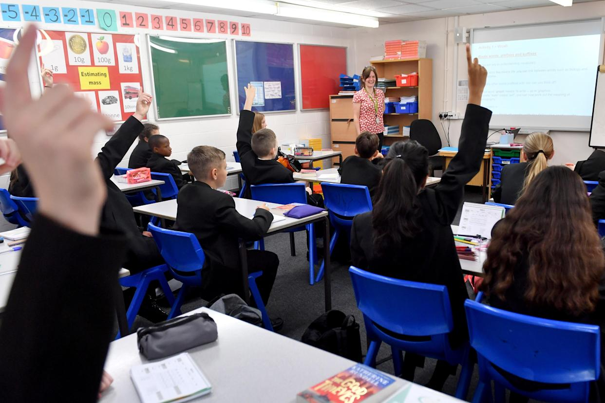 STALYBRIDGE, ENGLAND - SEPTEMBER 09: Pupils raise their hands in a lesson as they return to school at Copley Academy on September 09, 2021 in Stalybridge, England. Senior school pupils, returning to school across the UK during the second year of the worldwide Coronavirus pandemic, are taking part in a mass program of lateral flow tests designed to minimise the risk of spreading Covid-19. (Photo by Anthony Devlin/Getty Images)