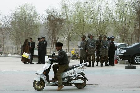 Police officers check the identity cards of a people as security forces keep watch in a street in Kashgar