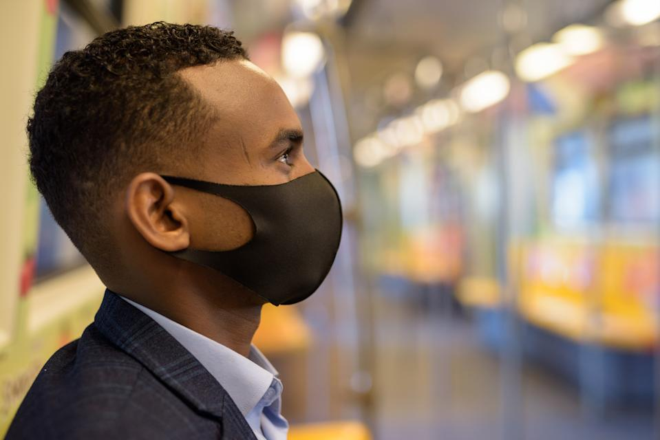 Portrait of young African businessman with mask for protection from corona virus outbreak social distancing inside the train