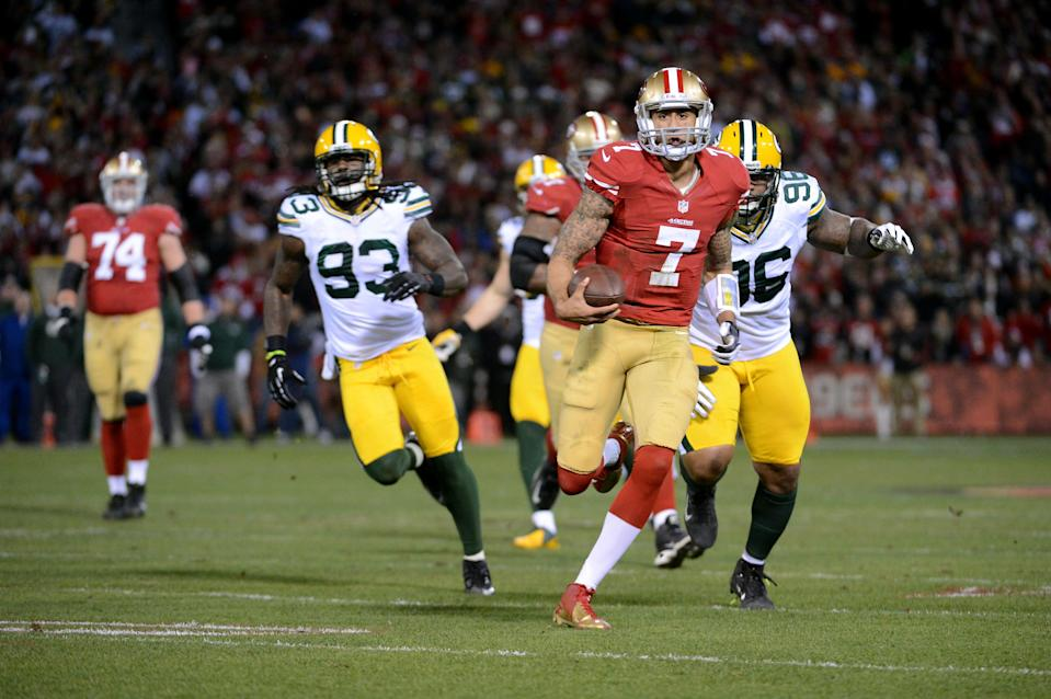 Colin Kaepernick evades Packers defenders during a 2013 NFC divisional playoff game. (Getty)