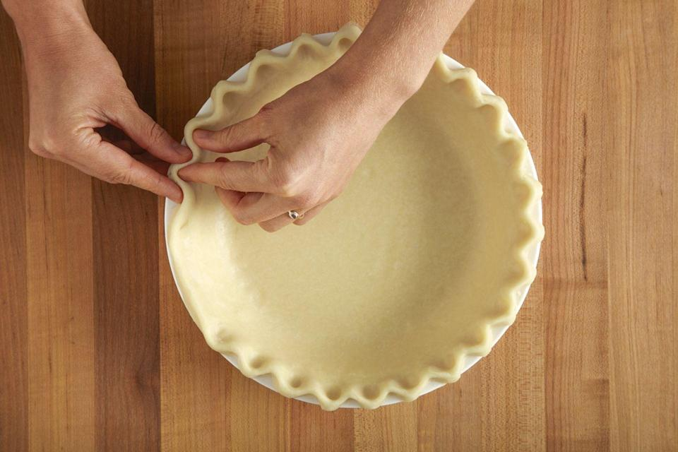 <p>Place a finger (or two, for a larger crimp) against the inside edge of the pie dough, then use the thumb and index finger of the other hand to press the pastry into flutes.</p>