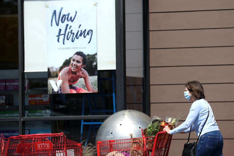 LARKSPUR, CALIFORNIA - APRIL 02: A pedestrian walks by a now hiring sign at a The Vitamin Shoppe on April 02, 2021 in Larkspur, California. According to a report by the Bureau of Labor Statistics, the U.S. economy added 916,000 jobs in March and the unemployment rate dropped to 6 percent. Leisure and hospitality jobs led the way with 280,000 new jobs followed by restaurants with 176,000 jobs and construction with 110,000 new positions. (Photo by Justin Sullivan/Getty Images)