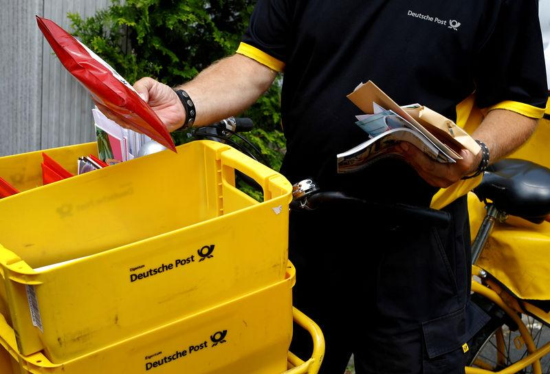 FILE PHOTO: A postman of German mail services Deutsche Post AG delivers mail in Hanau