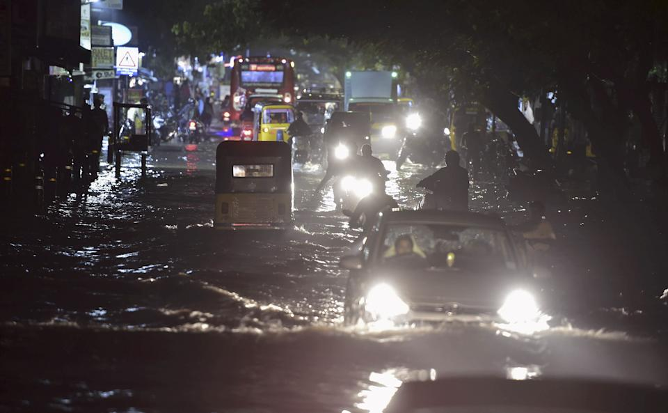 Vehicles ply on a waterlogged road during heavy rain triggered by Cyclone Nivar, in Chennai, Tuesday, 24 November, 2020.