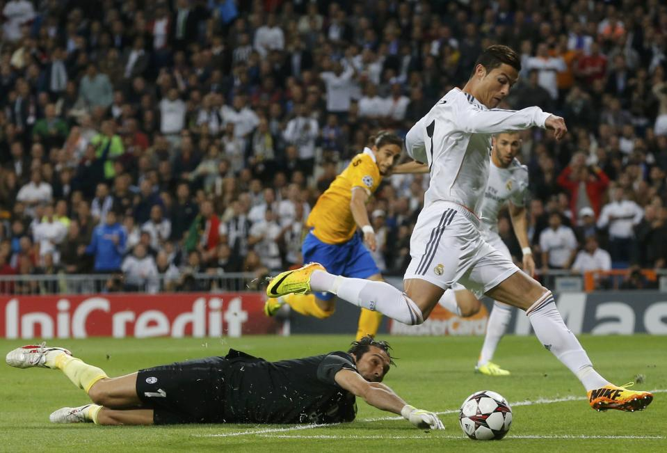 Real Madrid's Cristiano Ronaldo (R) eludes Juventus' goalkeeper Gianluigi Buffon to score a goal during their Champions League soccer match at Santiago Bernabeu stadium in Madrid October 23, 2013. REUTERS/Paul Hanna (SPAIN - Tags: SPORT SOCCER)