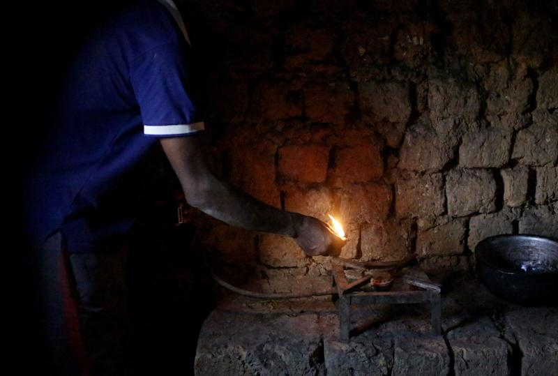 Etiene Twagirayezu, 60, lights his biogas digester in his home on November 18, 2017 in Rutabo, Rwanda. Twagirayezu says that before his digester, he'd spend up to 3 hours a day gathering 10 kilograms of wood, and saw kids get injured climbing trees and be late to school doing the same. He added he was happy his workload at home was reduced due to being able to use his cow's and pig's poo instead of wood as fuel, as well as about the resulting decrease of deforestation. (Photograph by Yana Paskova)