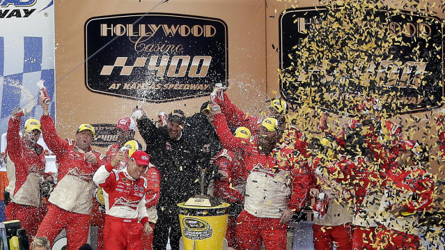 Driver Kevin Harvick, third from left in foreground, celebrates in victory lane after winning the NASCAR Sprint Cup series auto race at Kansas Speedway in Kansas City, Kan., Sunday, Oct. 6, 2013. (AP Photo/Charlie Riedel)