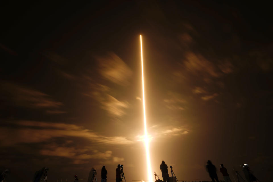 In this long exposure photo, photographers watch a SpaceX Falcon 9 rocket with the Crew Dragon space capsule lifts off from pad 39A at the Kennedy Space Center in Cape Canaveral, Fla., Friday, April 23, 2021. (AP Photo/Brynn Anderson)