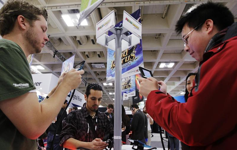 """FILE - In this March 8, 2012 file photo, attendees play the Nintendo game """"Mario Tennis Open"""" on a Nintendo 3DS console before its May release at the Game Developers Conference in San Francisco. The organizers of GDC, which kicks off Monday, March 17, 2014, at the Moscone Center in San Francisco and continues through Friday, have expanded the conference's advocacy-themed sessions with panels featuring such titles as """"Beyond Graphics: Reaching the Visually Impaired Gamer,"""" """"How to Subversively Queer Your Work"""" and """"Women Don't Want to Work in Games (and Other Myths)."""" (AP Photo/Paul Sakuma, file)"""