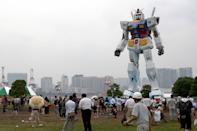 """Full Sized 'Gundam' Installed In Tokyo. 18-meter 'Gundam' is being installed at Shiohama Park in Tokyo, Japan. The hero robot of the popular animation series 'Gundam' is being built as the 30th anniversary of TV broadcasting. """"Gundam"""" was completed. A lot of sightseers come. (Photo by Yamada HITOSHI/Gamma-Rapho via Getty Images)"""