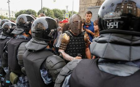 A man wearing a knight outfit walks past police officers blocking a street during a rally against planned increases to the nationwide pension age in St. Petersburg Russia